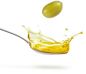 green olive falling on a splashing spoon of oil isolated on white