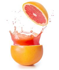 juice splashing out of a grapefruit isolated on white