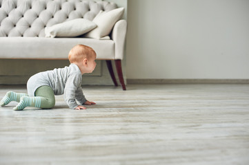 little baby boy crawling on floor at home