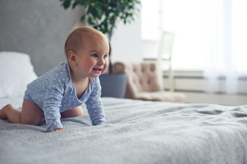 8 month old happy baby boy crawling on bed at home