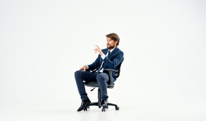 man sitting on a black chair on an isolated background