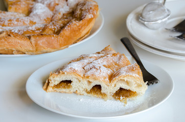 Piece of Ensaimada, coil-shaped flaky pastry from Mallorca, Balearic Islands. This is one of popular pastries in Spain eating at breakfast, snack time and dessert