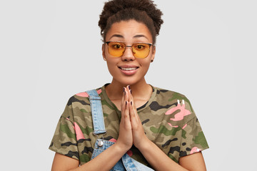 Calm beautiful dark skinned curly woman in trendy shades, keeps palms pressed together, has pleading expression, dressed in camouflage t shirt, poses against white background. Praying concept