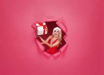 Young and beautiful Santa girl in a Christmas concept. Red background with a hole in paper.