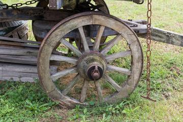 ruota di antico carro di legno e catena arrugginita primo piano