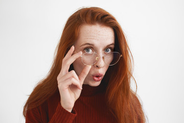 Horizontal shot of amazed astonished young European female with long ginger hair and freckles staring at camera in shock, lowering eyeglasses, can't believe her own eyes, seeing something curious