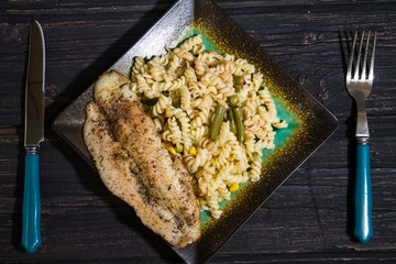 Pasta with delicious fish on wooden background