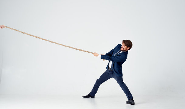 business man in suit pulls the rope