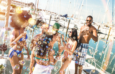 Multiracial friends group having fun drinking wine at sail boat party - Friendship concept with young multi racial people on sailboat - Happy travel lifestyle on luxury location - Warm bright filter