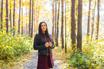 Young pretty woman in autumn park. Fall and season concept