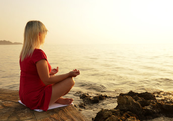 Woman practicing yoga by the sea at sunset.