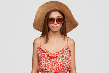Beautiful brunette woman in summer hat, dress, purses lips in discontent, feels displeasure, being discontent with weather conditions, wants to go ashore, models indoor against white background