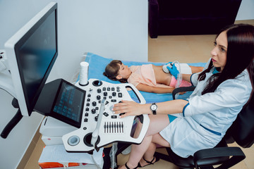 Medical exam of a little girl by ultrasound equipment