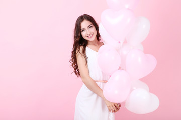 Young girl with heart balloons on pink background