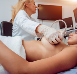 Gynecologist performing breast examination for her patient using ultrasound scanner. Sonography. Medical equipment healthcare. Ultrasound scanning.