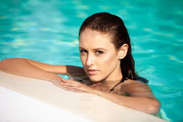 Beautiful young woman swimming in the pool on a hot summer day