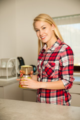 Beautiful young blond woman cooks coffee in kitchen