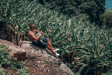 sports Guy in the jungle with a beautiful view of the sea in the hands of a large bunch of bananas . Thailand, Phuket island