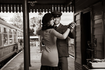 Attractive couple dance on railway station platform with portable record player