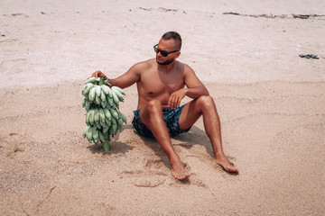 Sports man standing on the beach and holding a lot of bananas Green bananas in the hands of men.