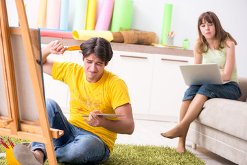 Young couple enjoying painting at home
