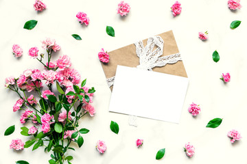 Creative layout made of pink rose flowers and blank greeting card with envelope. Flat lay. mock up. wedding invitation