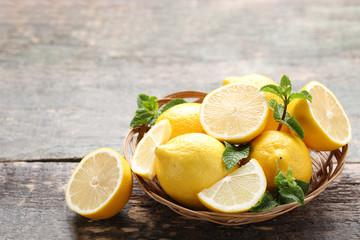Ripe lemons in basket on grey wooden table