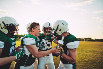Ecstatic young American football team celebrating with a champio