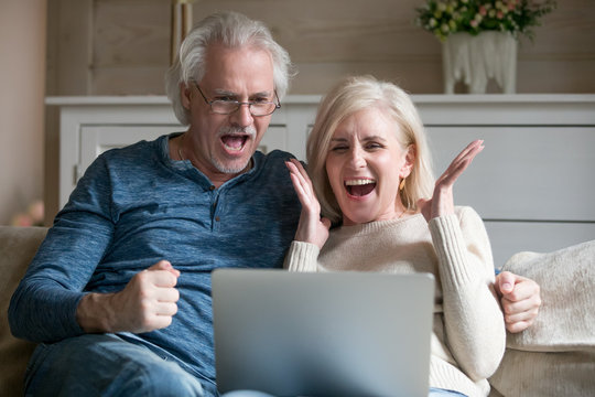 Excited senior middle aged old couple watching celebrating amazing victory winning online auction bid or bet together, elderly mature man and woman motivated by good news looking at laptop screaming