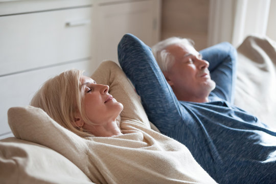 Calm senior mature couple relaxing on soft comfortable sofa having daytime nap together, carefree middle aged old family breathing fresh air enjoying no stress free peaceful weekend resting on couch