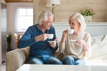 Happy senior old couple sitting on sofa in living room talking enjoying tea at home, smiling middle aged mature family chatting laughing drinking coffee having fun pleasant conversation together