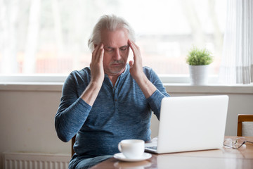 Tired fatigued middle aged senior man touching temples feeling headache migraine working on laptop at home, old elderly mature man trying to remember or focus suffering from memory loss disorder Wall mural