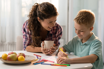 Smiling mother and son coloring together
