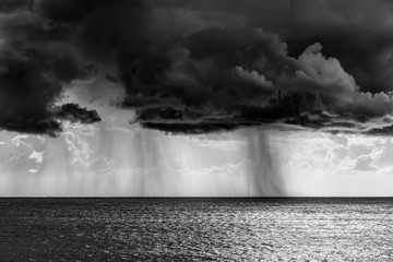 Fotobehang - Shower rain over the sea in black and white effect