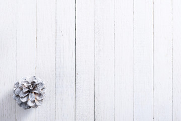 snow painted pine cone on rustic white wood table, Christmas decoration background