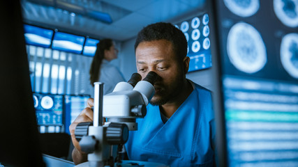 Medical Research Scientist Looking under the Microscope in the Laboratory. Neurologist Solving Puzzles of the Mind and Brain. In the Laboratory with Multiple Screens Showing MRI / CT Brain Scan