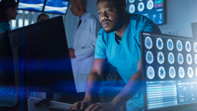 Male Scientist / Neurologist Working on a Personal Computer in Modern Laboratory. Research Scientists Making New Discoveries in the fields of Neurophysiology