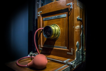 The old studio camera for using plates standing on a forked camera stand. Retro wooden camera at studio photographic studio.