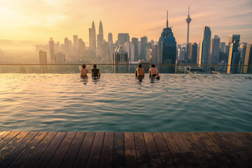 Photo Blinds City building Traveler looking view skyline Kuala Lumpur city in swimming pool on the roof top of hotel at sunrise in Kuala Lumpur, Malaysia.