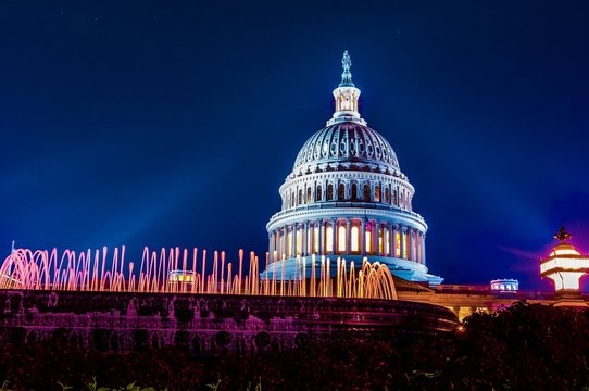 Dome of the marble United States capital building in Washington DC illuminated at night wiht glowing fountain in the foreground