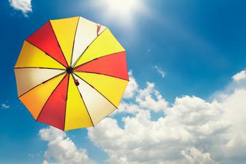 Yellow umbrella on blue sky