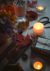 mug of hot cocoa with marshmallows,pumpkins  ,candles,gifts, bouquet on the old white table/autumn holidays concept