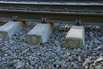 iron rails and concrete sleepers in fine gray rubble