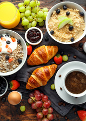Healthy Breakfast served with coffee, orange juice, croissants, egg, cereals, oatmeal and fruits.