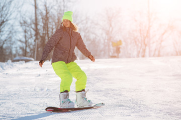 Winter sport activity, woman snowboarder riding on slope