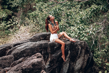 Young beautiful woman sitting on stones in the jungle and covers her bare Breasts with her hands