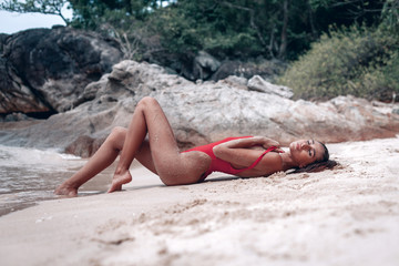 Young fit brunet girl  in red swimsuit lying  on the wet sand beach with out of focus rocks and palms in background. Kata beach, Phuket