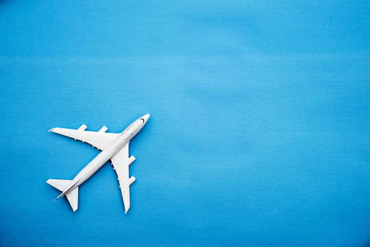Flat lay of miniature toy airplane on blue background minimal trip and travel creative concepts. copy space