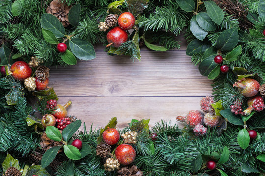 Christmas greenery wreath background with glittery apple ornaments on rustic wood