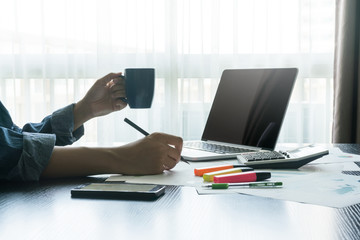 businessman writing business plan and holding coffee cup. finances and business concept